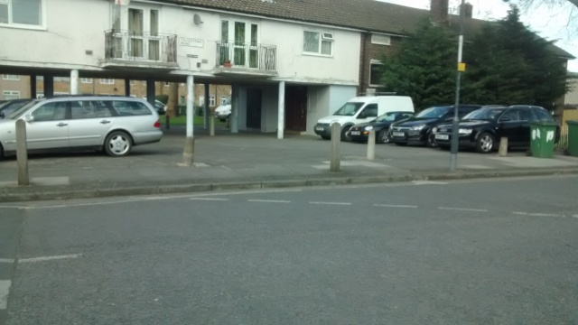 About 8 parked on paving with a van on grass behind
