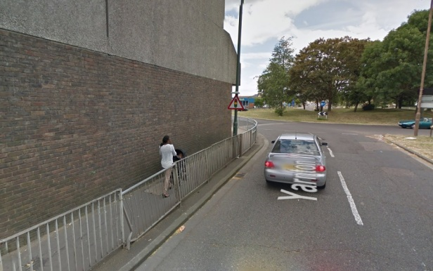 Narrow paving, large roundabout beyond forcing long detours to reach shops & housing